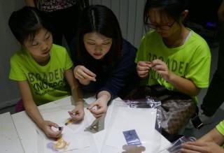 工作人員解釋電池、開關和小裝置的導電位置,然後讓學生試玩。