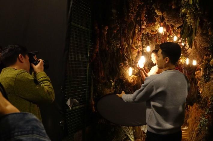 攝影師在酒吧的充滿燈泡的影棚內進行拍攝示範。