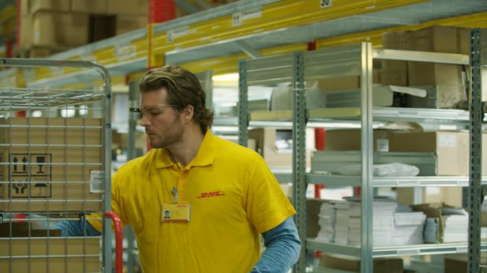 配戴該眼鏡的 DHL 員工正在倉庫中處理貨物。