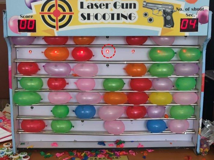 細心觀察,原來計分架上的有紅色燈作接收,擊中就會發出電能,引爆氣球。