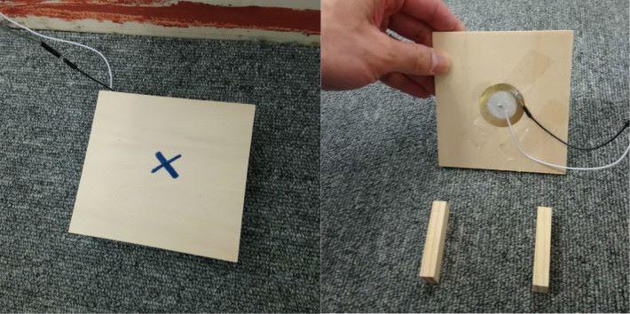 蜂鳴片貼在木板底部,木板面上的「x」位置預計為金屬小球下墜的位置。