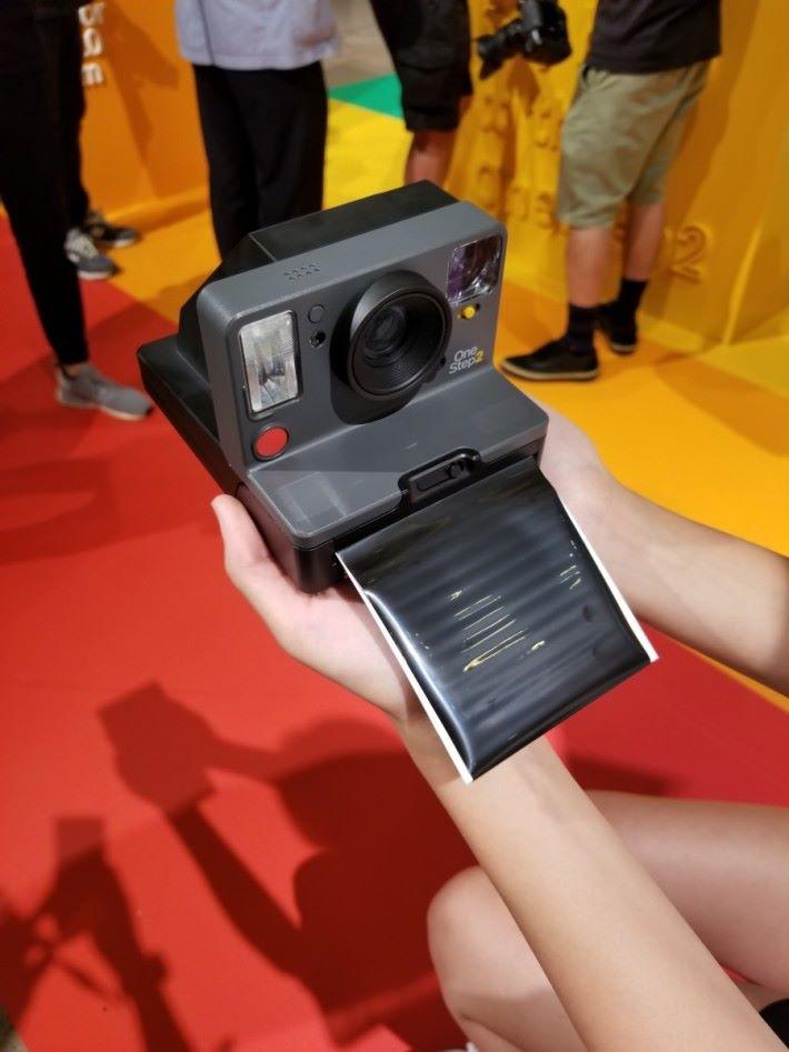 影完後相紙會前面走出來,揭起黑色的遮光簾便可取出相片。