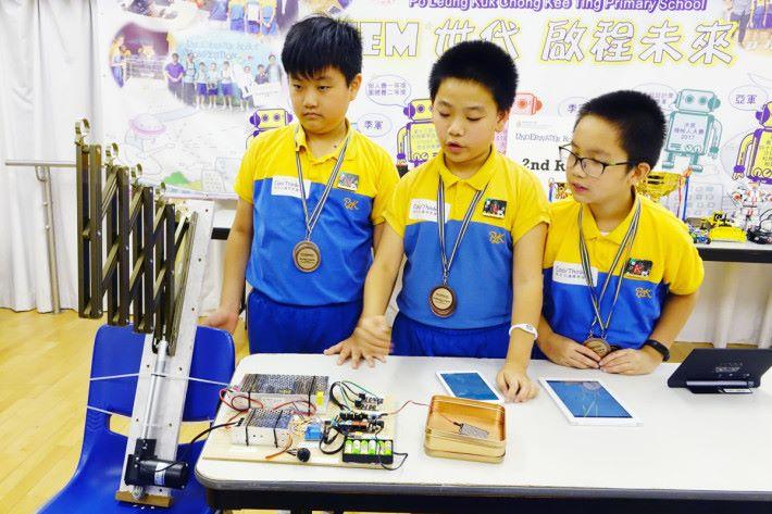 保良局莊啟程小學三位高小學生(左起)黃卓轁、胡瀚庸、陳漢雄合力製作自動曬衣架。