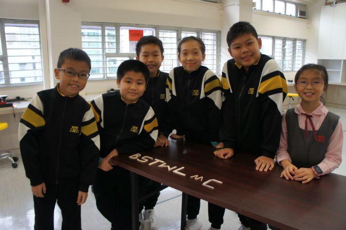 (左起)六位學生鄭灝言、王子俊、梁皓程、施恩慈、關學謙、吳映璇,花了大概十分鐘左右,與小記一起製作了學校縮寫的七個英文字母。
