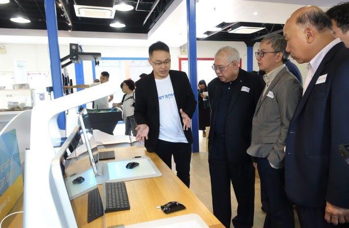 梁偉健(左)向鍾偉強(右二)及有份籌辦購物城的立法會議員黃定光介紹場內設施。