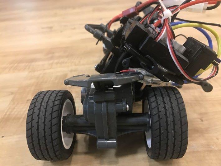 翻側時依靠伺服摩打驅動轉軸令車身左右搖擺至不同角色來改變行車方向,引導前輪向左右兩邊傾側來令遙控三輪車過彎。