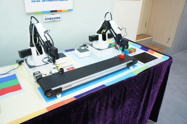配合設計,加入感測器,就可作運送識別。圖中設計是第一組機械臂會將物品放上運輸帶,第二組機械臂經由顏色感應器,將之調動到適當位置。