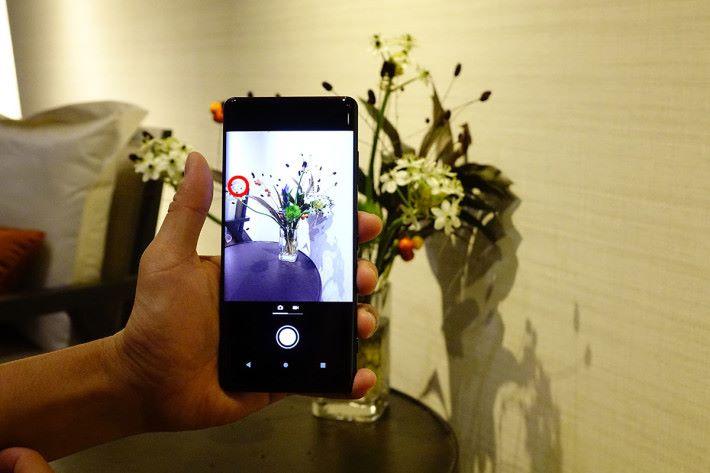 拍攝時對準主體後點兩下曲芒位,等於按下快門即時拍攝,於手指位旁會先出現相機圖示提示啟動了「側面感應」功能。