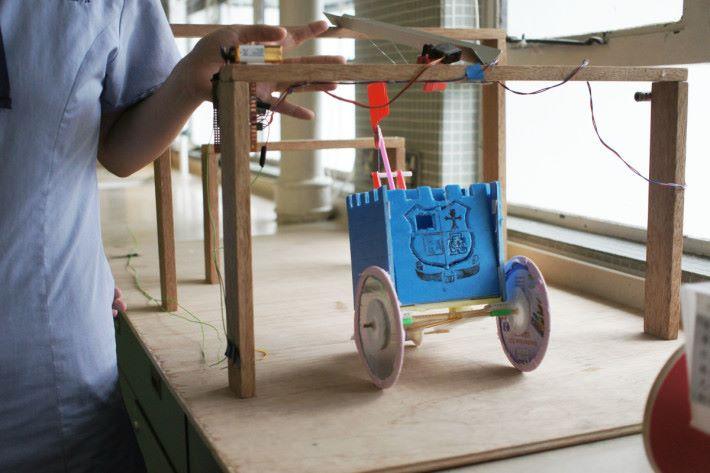 利用橡筋推動模型車向前前進,同時帶動線圈在特定位置靜止,讓模型車內的旗幟上升。