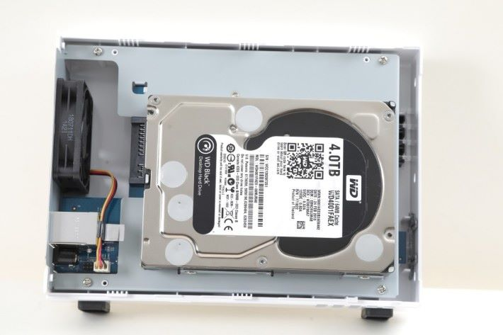 """推開側蓋,就能上螺絲安裝 3.5"""" 硬碟。也支援 2.5"""" 硬碟或 SSD,但需另外購買 2.5"""" 固定器。"""