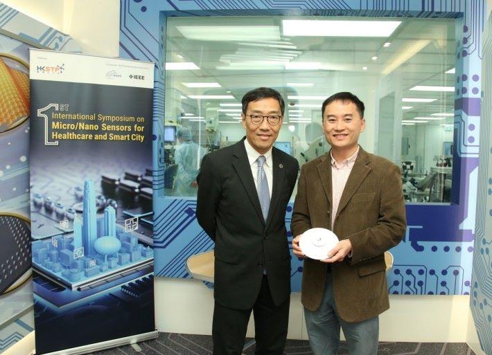 香港科技大學計算機科學及工程學系教授兼大學創業中心主任陳雙幸(右)與香港科技園公司行政總裁黃克強展示由科大研發的 SmartAP,透過 Wi-Fi 技術偵測及追蹤人流。