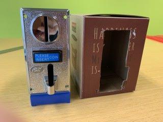 1. 找個沒用的瓦通紙盒,在正面和底部按投幣器的尺寸剪個洞;