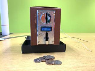 2. 把投幣器收藏在紙盒裡,放在錢箱上;