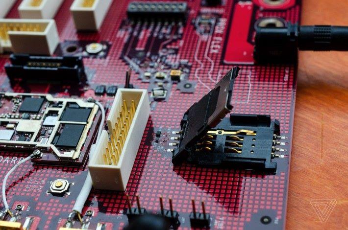 電話卡插槽,圖左端的就是無線模組,白色的接頭是用來連接測試器材的。(來源: The Verge )