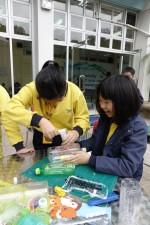 學生們坦言曾以為黐實膠樽作船身就可以,但當加入摩打時,船出現自動解體。相片中學生們經討論後,正嘗試其他組裝方法。