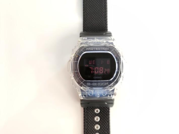 全透明錶殻設計,錶面以黑底暗紅色字顯示時間等資訊。
